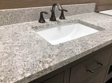 Remodeled bathroom vanity with granite counter and white sink.